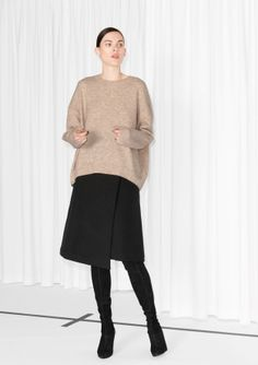 Knitted from soft wool, this sweater has an asymmetric cut and a oversized, wide silhouette.