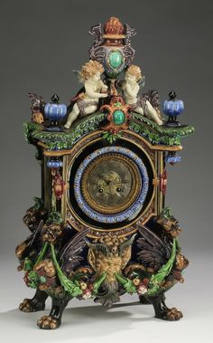 Renaissance Revival majolica mantel clock by Hugo Lonitz with a movement by Japy Frères, having a flaming urn finial flanked by griffons and putti, above an arched crest with finials, centering a brass dial having Roman numerals framed with an acanthus molding, above a horned pan mask, rising on monopodial winged griffin supports with hairy paw feet connected by fruited swags, majolica case is unmarked, the movement is marked Japy Frères.