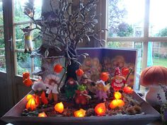 Beautiful nature table, love the lanterns around bulbs of a string of Christmas lights