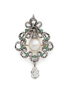 A natural pearl, emerald and diamond brooch/pendant, circa 1905. Designed as a wreath, the rose and old brilliant-cut diamond bow surmount, to a similarly-cut ribbon surround with circular-cut emerald highlights, enclosing a natural saltwater pearl, and suspending a pear-shaped diamond drop.