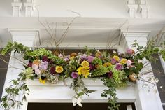 A transom window arrangement, resting on the top of the door frame. Bright colored flowers include, sunflowers, antique green hydrangea, hot pink spray roses, bells of ireland, orange roses, yellow roses, pink roses, pink mini carnations, pink peonies, curly willow, and local foliage, creates a bright, spring garden feel to this New Orleans home.