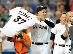 Miami Marlins starting pitcher Jose Fernandez celebrates his teammates no-hitter by holding up Alvarez's jersey.
