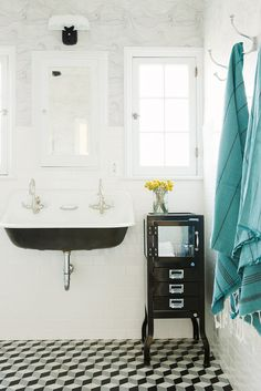 Black and white bathroom with hanging turquoise towels.