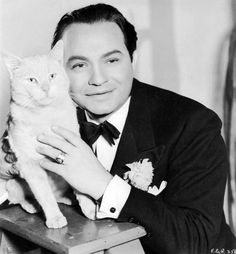 Tough-guy actor Edward G. Robinson affectionately posing for a portrait with his very cool cat.