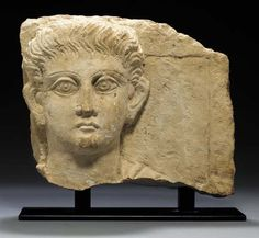A PALMYRENE RELIEF WITH THE HEAD OF A YOUTH   Circa Mid 2nd Century A.D.   From a funerary relief, the deceased depicted wearing a mantle over his left shoulder, the fleshy face with wide, flat features framed by the large ears, with long wavy locks of hair brushed back, the sharply incised brows arching above large lidded eyes, the irises and pupils deeply incised, the small mouth with thin pursed lips, the filtrum indicated  11 in. (27.9 cm) high