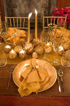 Gorgeous holiday dinner napkins are folded and held into place with a gold ribbon and two small ornaments.