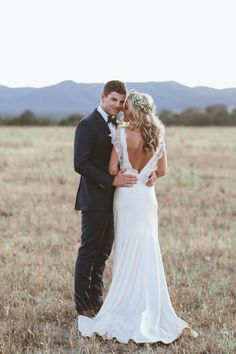 """Sarah Janks' """"Eva"""" dress has a relaxed column silhouette and a stunning back detail that makes the bride look equally gorgeous from every angle! It combines boho style with a more traditional style, and we love everything about it! The couple looks so in love, and we think this is so reminiscent of the American dream wedding! (Photo by Edwina Robertson)"""