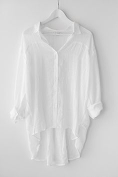 Long sleeve button up and collared top with an oversized fit. Roll up sleeves with button closure. Made with lightweight non-stretch material. Wear normally or with the front tied in a knot. A simple top that you can wear so many ways! Available in off-white or blue denim. 70% Polyester 20% Cotton 10% FCAX Imported