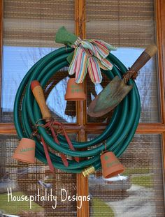 Garden Hose Wreath with spade and claw, gloves and pots.  Could also add seed packet, wire pot in upright position, add flower vine?  Maybe a rubber lizard?