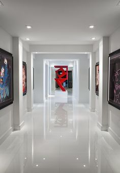 "A veritable art gallery, this hallway dazzles with six ""Myths Series"" screen prints by pop artist Andy Warhol. Welded and painted Ferrari red, the industrial sculpture designed by homeowner Adrienne Krieger stands out like a cherry on a sundae. Küchen Design, Floor Design, Tile Design, Design Room, Florida Design, Room Tiles, Marble Floor, Tile Floor, White Tiles"