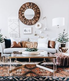 Yule style!! Noel Christmas! Simple real Christmas Tree in a pot plus Winter white walls plus Modern Bohemian Chic style!! White sofa plus lots of color, pattern and texture! See how the raw wood round mirror creates a real focal point on the all-white gallery wall!