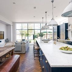 The navy blue kitchen zone encompasses the contemporary country design, including a stunning six-metre-long marble-topped island and breakfast bar with plenty of space to receive guests. The white quartz worktop looks super fresh against the navy blue uni Open Plan Kitchen Living Room, Navy Kitchen, Kitchen Decor, Long Kitchen, Kitchen Units, Kitchen Modern, Kitchen Cabinets, Modern Farmhouse, Sofa In Kitchen