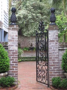 Beautiful brick and wrought iron gate with pineapples on top of pillars. Love this southern style!