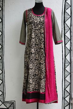 an elegant long anarkali in black & white with electric pink trims; a perfect wear to host a party! the wide border shows running stitches that adds inte
