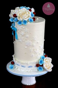 """Here's the wedding cake I made for a bride & groom and their small family dinner celebration. The bride's colors were ivory, marine blue and a little copper, and she wanted to incorporate snowflakes in some way. This design quickly formed in my head, along with the idea of the hanging heart key. This is a """"double barrel""""...I really wanted to have enough room for the snowflake swoop, so I thought this might be perfect. It's finished in buttercream. I should have the rose tutorial up on my fb…"""