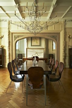 La salle à manger avec sa perspective digne d'un manoir anglais. Si la longue table n'est pas signée, les chaises qui l'entourent sont de Tom Dixon, tout comme la suspension filiforme – un motif qui reprend celui de la chaise Pylon. Tout au fond, une peinture de Jean Arp surplombe une sculpture de Zaha Hadid. Sur la table, un chandelier d'Arik Levy.