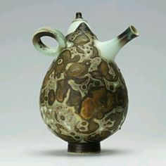 This is a porcelain miniature teapot by Geoffrey Swindell which has been thrown in several sections.