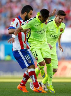 Arda Turan of Atletico Madrid battles with Neymar and Lionel Messi of Barcelona during the La Liga match between Club Atletico de Madrid and FC Barcelona at Vicente Calderon Stadium on May 17, 2015 in Madrid, Spain.