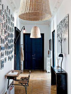 天然の床材や、鋳物のラジエーターが並ぶナチュラルで居心地のいい空間の中に、巨大な籐製の吊り照明が連なるインパクトのあるエントランス。イタリア出身の女性インテリアデザイナー、パオラ・ナヴォーネが手掛けたこの照明アイテムは、サラの一番のお気に入り。通路の壁には、フランスで高い人気を誇るフォトグラファー、ヴァレリー・ナイトの木の写真と対面するように、ポラロイドコレクションが一面に飾られている。 サラはこの家で、適正な色のミックス、偏愛する現代アーティストの作品展示、デザイナーズ家具の見事なセレクトによって、クラシックな空間をモダンに変化させることに成功!