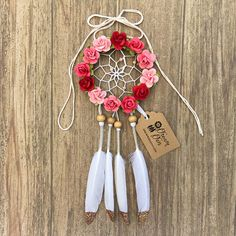 Handmade small dream catcher with beige suede lace exterior covered in different shades of pink mulberry paper rose flowers with a white interior. Pink beading accents in the interior with wooden beads holding the white, rose gold glitter tipped feathers in place. The diameter of the hoop measures 3 inches. String is long enough for you to hang the dream catcher over a rear view mirror of a car, and adjustable.  Perfect size for hanging over a rear view mirror in a car or over a bed!  Dream…