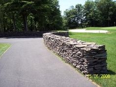 Dry stacked stone walls finish off just about any landscape. No matter when they were built, they always look like they have been there forever. This drystack stonewall graces the entryway to a golf course.  Picture compliments of www.stonestackers.com