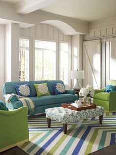 The color scheme in this living room seems to have originated with the fabric used on the ottoman as inspiration. The disparate shades of blue & green work well together & give a fresh and informal look to the space. I also love the window & the pediment built on top...V