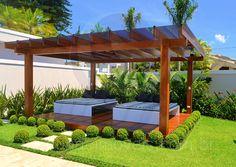 Em meio ao lindo projeto de paisagismo do jardim, um pergolado em madeira abriga duas day-beds e oferece boa sombra para o pleno relaxamento.