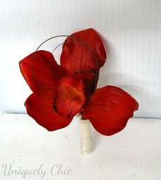 A beautiful boutonnière perfect for any fall wedding or special event. Designed with a bright burgundy red real touch orchid, with a sheer ivory stem wrap finished with a burgundy sash and pearl pin.   #orchidboutonnniere #boutonniere #groomboutonniere #groomsmen #weddingboutonniere #red #accessories #weddings #etsy