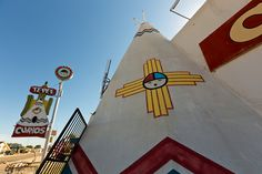 The large concrete teepee that marks the entrance to the TeePee Curio Shop, along Route 66 in Tucumcari, New Mexico.  The shop is an old gas station and gift shop that was built in 1944. When Route 66 was widened in 1959, the gas pumps were removed but the teepee entrance was added. The elaborate neon sign was added in the 1960s. Travel New Mexico, Old Gas Stations, Gas Pumps, Route 66, Road Trips, Entrance, 1960s, Concrete, Neon Signs