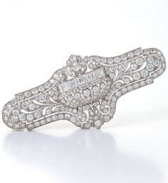 An American Art Deco platinum brooch with diamonds by E. M. Gattle & Co., circa 1920. The brooch set with 168 old European-cut diamonds and 5 square-cut diamonds centring a dimensional jardinière flanked by pierced foliate elements with a millegrain set diamond border, mounted in platinum. #Gattle #ArtDeco #brooch