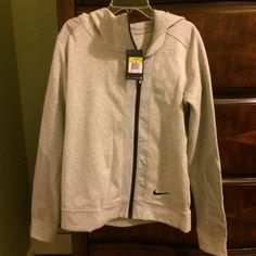 NWT GRAY NIKE ZIP UP HOODIE NWT NIKE GRAY ZIP UP HOODIE. SIZE SMALL BUT CAN FIT A MEDIUM, DEPENDS HOW YOU LIKE THE FIT OF YOUR SWEATSHIRTS. LIGHT GRAY IN COLOR WITH GRAY MESH MATERIAL ON SLEEVE, ZIPPER AREA AND SHOULDER ONTO TOP BACK. RETAILS FOR $75. Nike Jackets & Coats