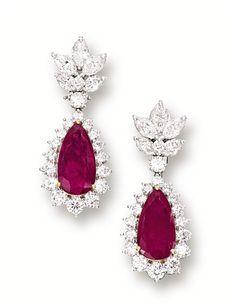PAIR OF RUBY AND DIAMOND PENDENT EAR CLIPS. Each suspending on a pear-shaped ruby altogether weighing approximately 10.30 carats, surrounded by brilliant-cut diamonds, to a surmount set with marquise-shaped and brilliant-cut diamonds, the diamonds altogether weighing approximately 8.60 carats, mounted in platinum and 18 karat yellow gold.