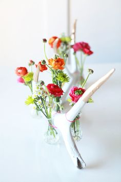 To make the floral antler decoration first paint your antler white and then dip the tips into bright gold paint. Find small vases to use for the flowers and attach them to the antlers in succession with bright neon string. Fill the small vases with spring flowers. Easy, bright and pretty!