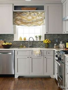 Creating a kitchen scheme with little difference between the colors ofwalls, countertops, cabinetry, and woodwork makes a space appear larger than it really is. Here, the cabinets, trim, and backsplash are close in color value -- a soft gray-green -- so the eye doesn't trip over sudden shifts from dark to light. The effect is serene and expansive.
