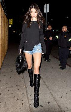Kendall Jenner wears a sweater, denim cutoffs, knee-high boots, and a top-handle bag