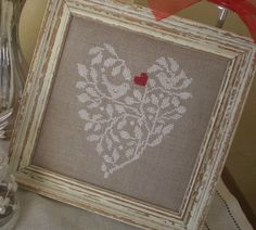 . de X...  --White branches and birds with red heart in a heart shape on linen. Lovely
