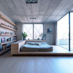 Neutral minimalist bedroom with low bedframe and book shelf