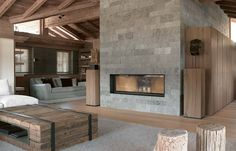 Beautiful chalet design in Austria combining natural materials of timber and stone with comfortably detailed modern interiors by Bernd Gruber Architects.