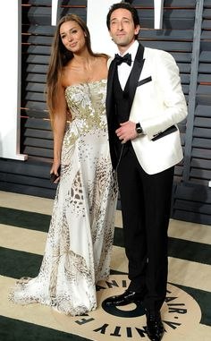 Lara Lieto & Adrien Brody from 2015 Oscars After-Party Looks (Plus Viewing Parties!)  In a printed white gown (Lara) and Dolce & Gabbana tuxedo (Adrien).