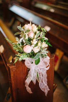 Flower posey on the ends pf the pews in the church - Image by Hayley Savage Photography - Pronovias 'Leonela' Wedding Gown & Coast Bridesmaid Dresses with No.1 by Jenny Packham Accessories in a Marquee at Hill Place with Pink & Grey Colour Scheme & Church Flower Arch.