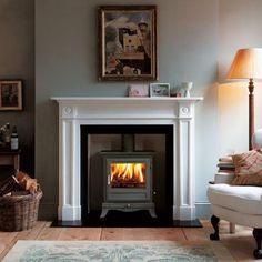 manteau de cheminée, poêle, peintures et fauteuil blanc vintage
