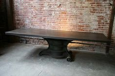 Gorgeous. o. m. g.    Vintage, industrial work table with massive cast base and wheels.    Can be found at Cleve­land Art.
