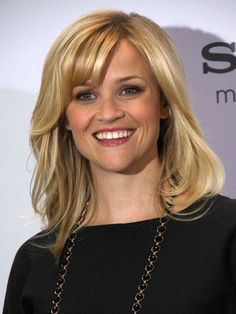 Reese Witherspoon's wavy mid-length hairstyle with side-swept bangs | allure.com