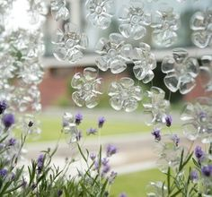 Pretty up your garden with these plastic bottle flowers...just cut the bottom from water bottles and string together!