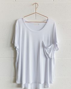 Basic White Tee - Blossom & Glow Maternity.  You asked for it, so here it is, the Basic White Tee!  We love this basic for layering during winter.  A soft jersey fabric, and slightly longer length at the back, its fit is perfect for all shapes and sizes.  Team it with our joggers, or skinny jeans, add a pair of cons, and you've got the perfect weekend look!  Also available in white stripe, grey, charcoal, and black stripe.