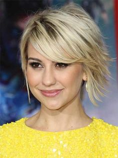 choppy layered haircut in blonde with darker root showing through and strong side bangs