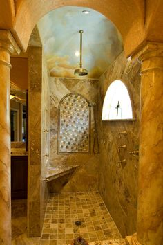 With arched accents and a warm, earthy color palette, this walk-in shower exudes Tuscan elegance. A rain showerhead, handheld showerhead and corner seat make for a luxurious shower experience.