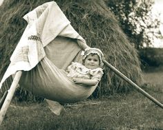 Slovakia 1952 - while the mother is working, child has a great time in the makeshift crib :)