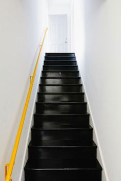 Exemple d'escaliers en bois repeints en noir qui a donné l'occasion de repeindre la rampe elle aussi en jaune lumière qui réveille les murs blanc.