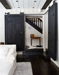 black sliding barn door, how cool that it slides closed into the corner! I can see chalkboards/pinboards hidden behind those doors.